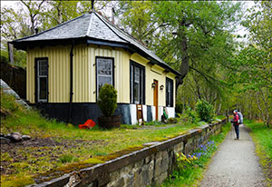 Walker on the Deeside walk path looking at a restored station house, now a home.Restored railway